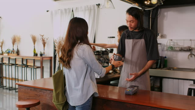 young asian woman customer giving her own coffee cup to asia man barista and making contactless payment through smart phone at counter in coffee shop cafe, zero waste concept - reduction stock videos & royalty-free footage