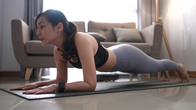 young asian woman doing a yoga plank at home - only young women stock videos & royalty-free footage