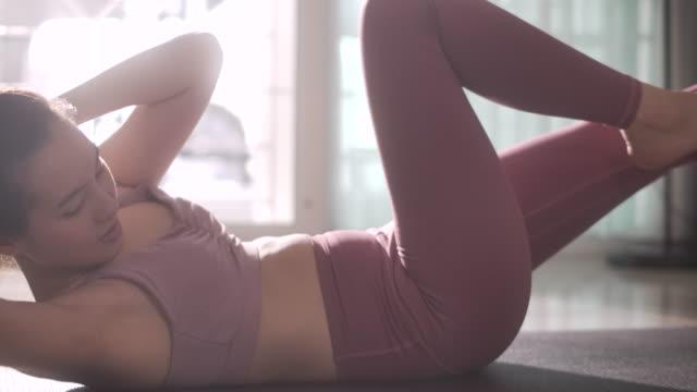 stockvideo's en b-roll-footage met jonge aziatische vrouw die cardio crisscross oefening voor abs doet die op sportenmat binnen liggen, langzame motie - pilates