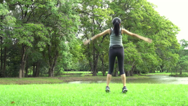 Young asian woman doing jumping jacks fitness exercise workout at park.