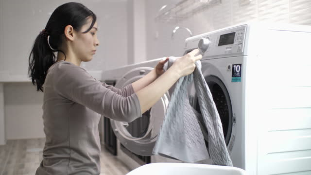 young asian woman doing laundry at home - stereotypical homemaker stock videos & royalty-free footage