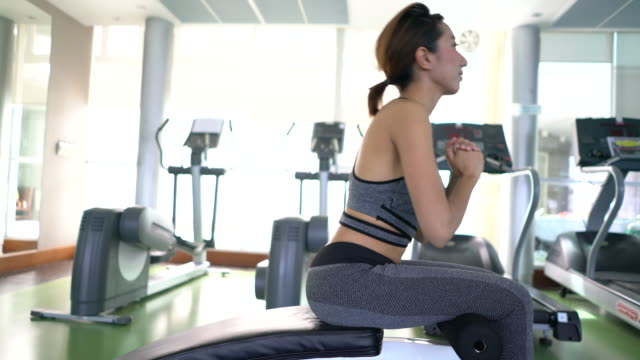 Young asian woman doing sit-ups exercising at Gym