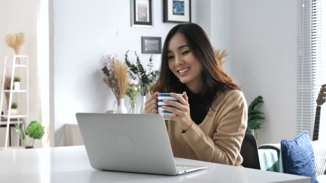 Young Asian woman drinking coffee and using laptop, Working from Home