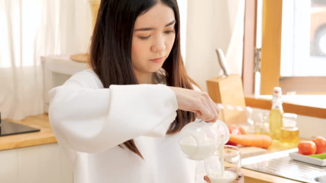 young asian woman drinking milk in kitchen. - vitamin a nutrient stock videos & royalty-free footage