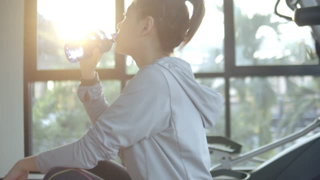 young asian woman drinking water after fitness exercise . - bottiglia d'acqua video stock e b–roll