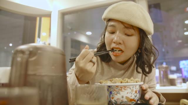 vidéos et rushes de jeune femme asiatique mangeant un boeuf japonais sur un bol de riz, japon - blog