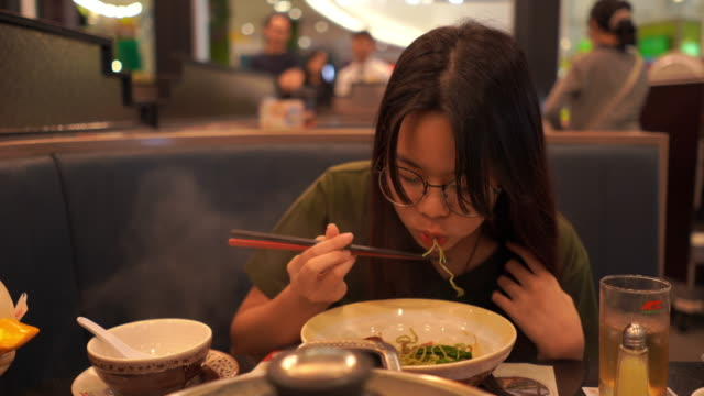 Young Asian woman eating food with chopsticks , Sukiyaki , Shabu-shabu