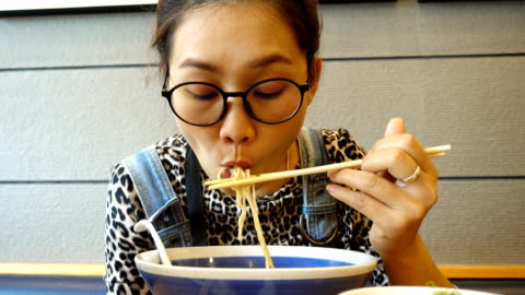 young asian woman eating ramen noodles. - noodles stock videos & royalty-free footage