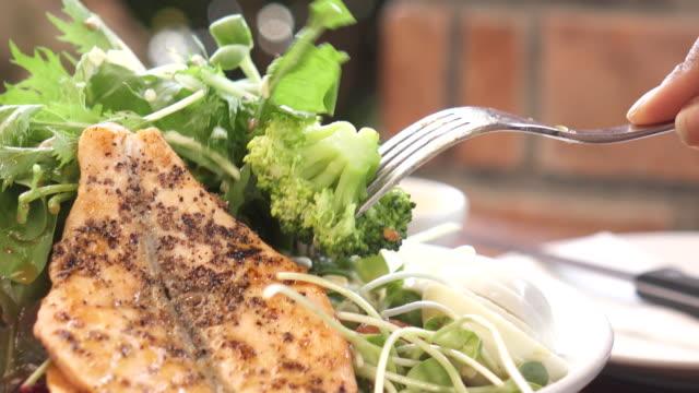 vídeos de stock e filmes b-roll de young asian woman eating salmon salad - cortado em filete