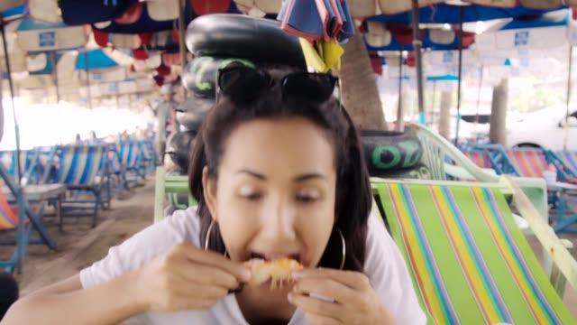 vidéos et rushes de jeune femme asiatique mangeant des fruits de mer et salade de papaye thai food à la plage. émotion heureuse. - goûter