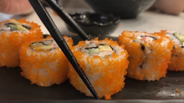 young asian woman eating sushi with chopsticks , california roll , japanese food - sushi video stock e b–roll