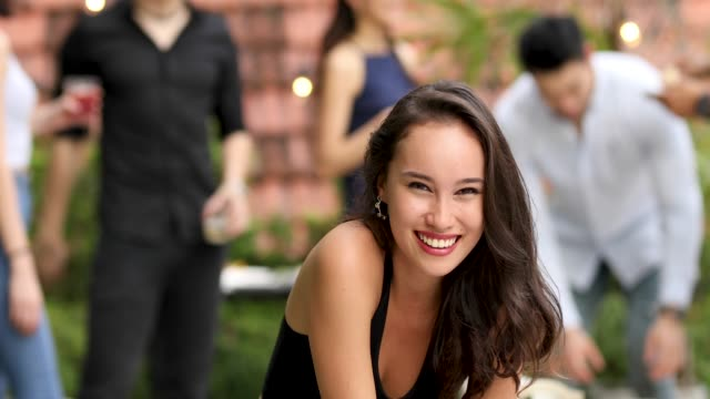 young asian woman enjoying drinks and food at rooftop party - cultura malesiana video stock e b–roll