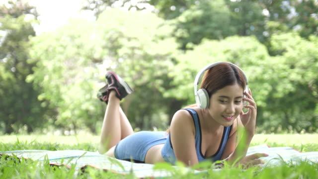 Jonge Aziatische vrouw genieten van muziek In Tuin, Slow motion