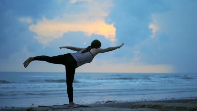 vídeos y material grabado en eventos de stock de joven asiática haciendo ejercicio en la playa - posa del loto