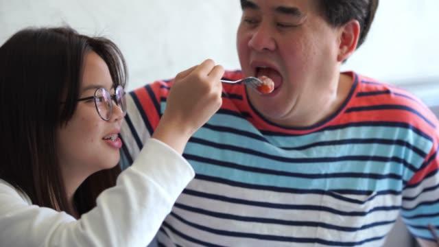 vídeos de stock, filmes e b-roll de jovem mulher asiática dando comida para o pai - alimentando