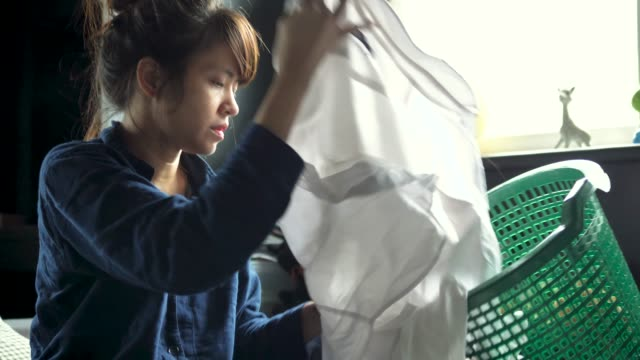 young asian woman folding laundry on the bed at home. - folded stock videos & royalty-free footage