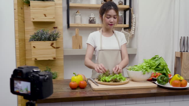 young asian woman food bloggers talking while recording video to preparing green salad in kitchen, tutorial video to social network by internet at home concept - detox stock videos & royalty-free footage