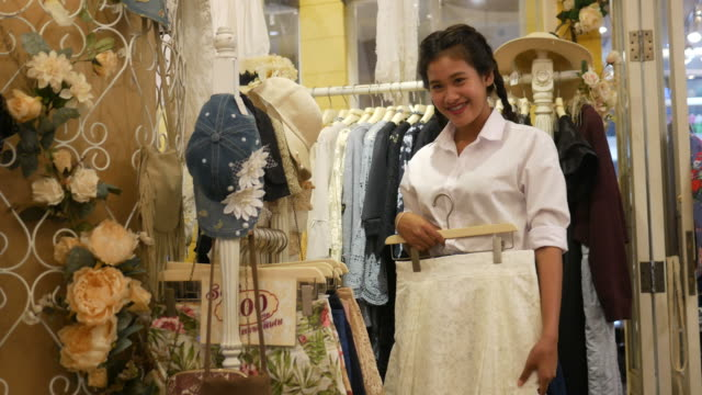 young Asian woman having fun shopping in boutique