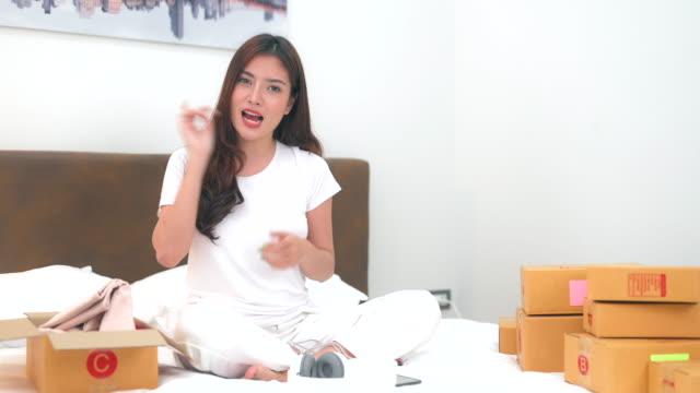 vídeos de stock, filmes e b-roll de jovem asiática ter transmissão ao vivo para vender produto nas mídias sociais usando celular e câmera para gravação no quarto em casa - blogar