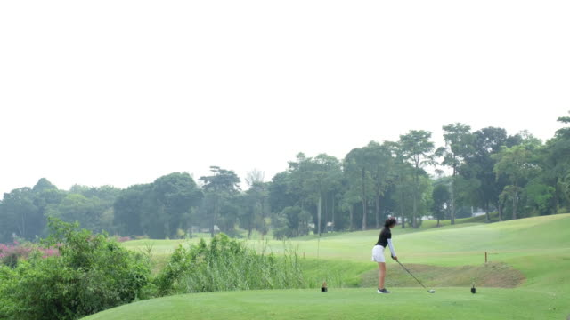 young asian woman hits the perfect golf shot - golf swing women stock videos & royalty-free footage