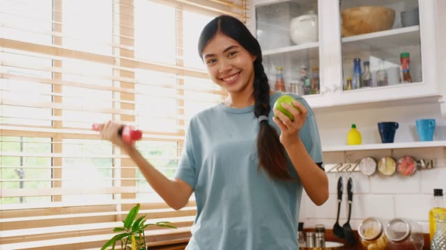 young asian woman holding dumbbell and green apple while exercising in kitchen at home, peolple and healthy lifestyles - dumbbell stock videos & royalty-free footage