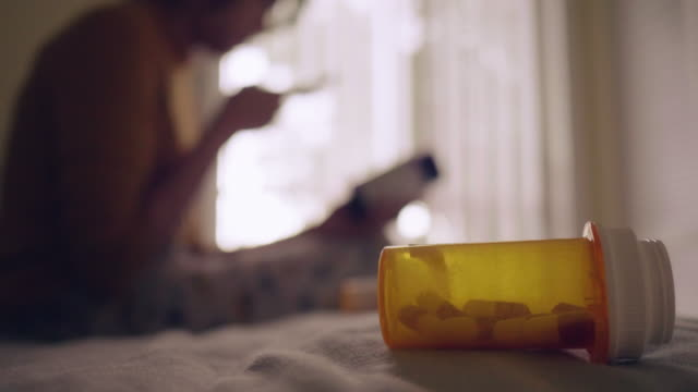 young asian woman holding pill bottle and talking on mobile phone in bedroom - label stock videos & royalty-free footage