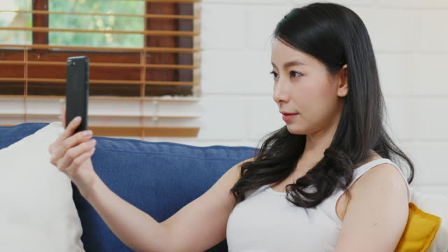 young asian woman holding smart phone as biometric verification and face detection, innovations and technology, people and technology lifestyle - human face photos stock videos & royalty-free footage