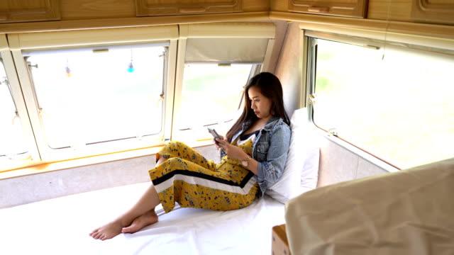 junge asiatische frau in einem wohnmobil - wohnmobil stock-videos und b-roll-filmmaterial