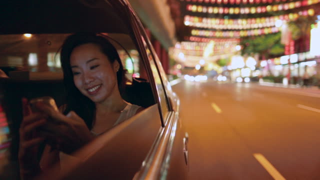 TS Young Asian woman in a car at night, texting.