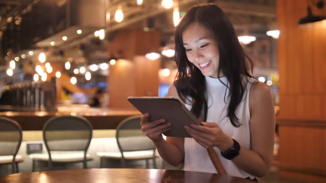 young asian woman in casual clothing using digital tablet touchscreen computer in cafe - businesswoman stock videos & royalty-free footage