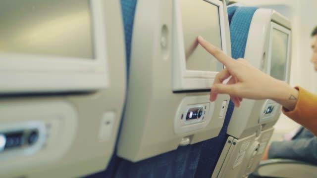 junge asiatische frau in kopfhörer während des fliegens im flugzeug - sitz stock-videos und b-roll-filmmaterial
