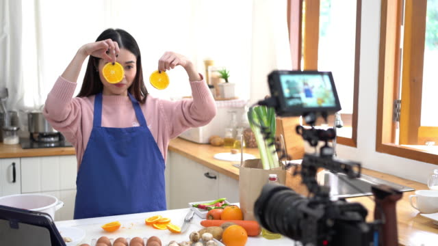 young asian woman in kitchen recording video on camera. - stream stock videos & royalty-free footage