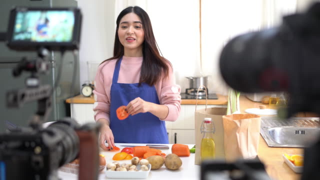 young asian woman in kitchen recording video on camera. - tutorial stock videos & royalty-free footage