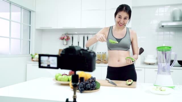 ung asiatisk kvinna influencer vlogger i idrott kostym göra juice eller frukt smooties i köket. - följa rörlig aktivitet bildbanksvideor och videomaterial från bakom kulisserna