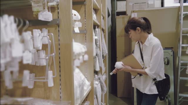 若いアジア女性がスーパーで家庭用品を選択します。 - 書店点の映像素材/bロール
