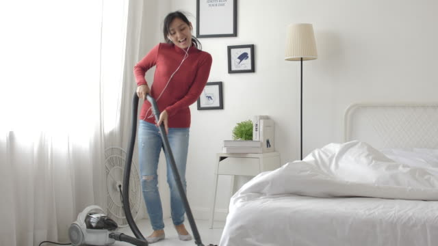 young asian woman is dancing and singing listening to music through headphones during housecleaning at home - vacuum cleaner stock videos & royalty-free footage