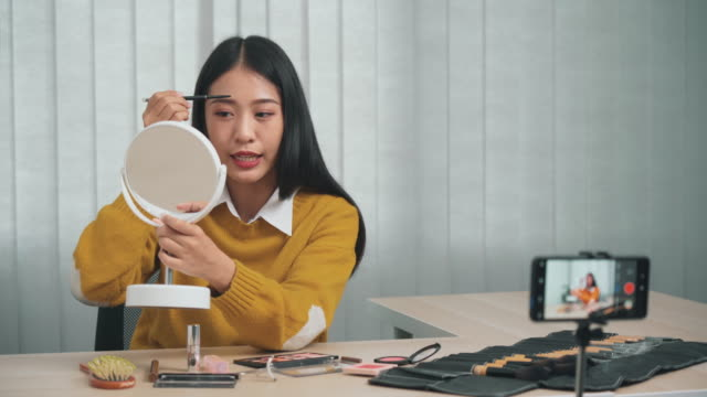 vídeos de stock e filmes b-roll de young asian woman is demonstrating how to apply makeup to her social media friends via her smartphone in the vlogging at home. - blush