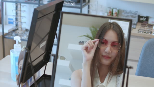 young asian woman is looking her self in the mirror while trying new eyeglasses. - sunglasses stock videos & royalty-free footage