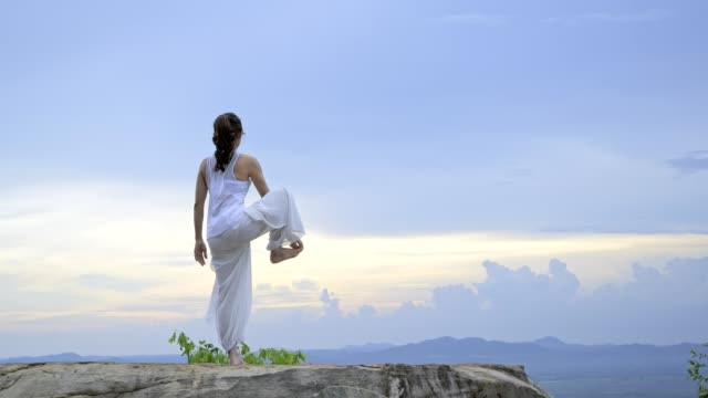 young asian woman is practicing yoga at mountain sea when sunset. - wellbeing stock videos & royalty-free footage