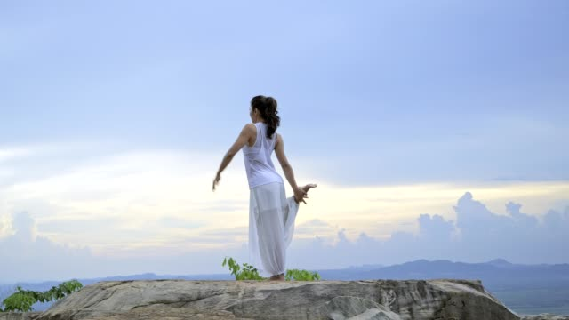 young asian woman is practicing yoga at mountain sea when sunset. - postura video stock e b–roll