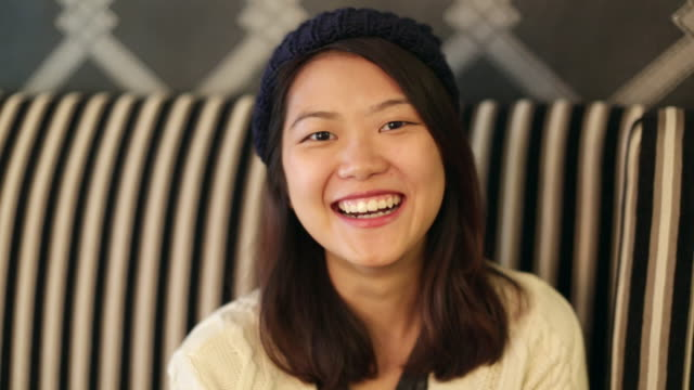 CU of young Asian woman laughing.