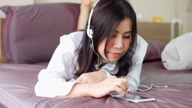 vídeos de stock, filmes e b-roll de jovem mulher ouvir música asiática - reclining