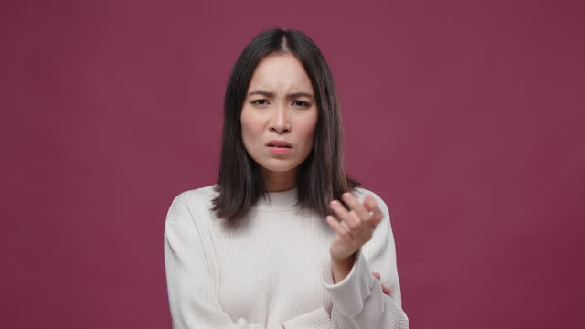young asian woman look dissatisfied against marsala copyspace - sour taste stock videos & royalty-free footage