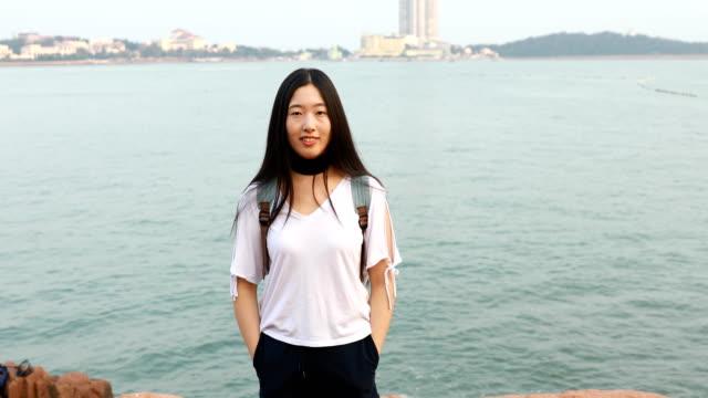 young asian woman looking at camera - 僅年輕女人 個影片檔及 b 捲影像