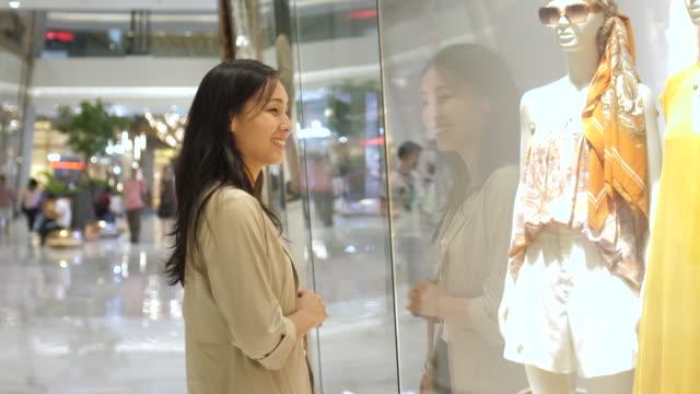 junge asiatische frau blick auf schaufenster, einkaufen in der mall, verkaufszeit - schaufenster stock-videos und b-roll-filmmaterial