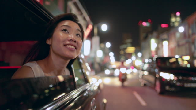 TS Young Asian woman looking out of car window at night.