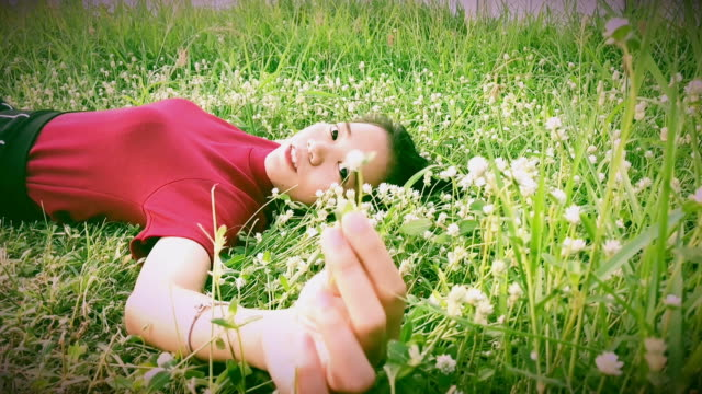 young asian woman lying down on grasses , slow motion - lying down stock videos & royalty-free footage