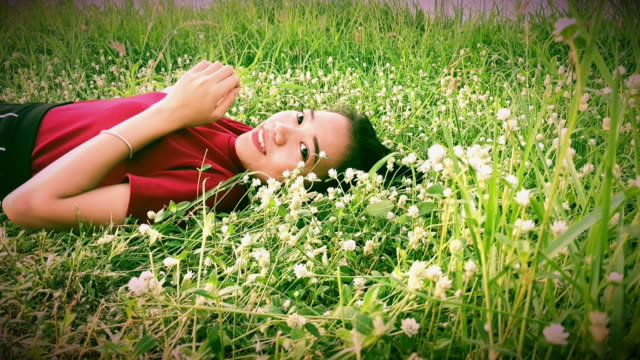 young asian woman lying down on grasses , slow motion - serene people stock videos & royalty-free footage