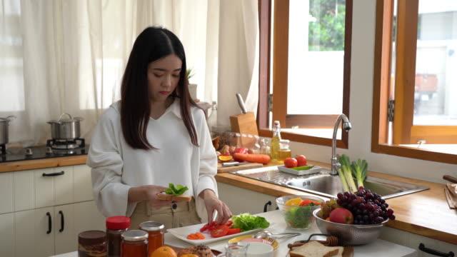 若いアジアの女性作りとサンドイッチを食べる - サンドイッチ作り点の映像素材/bロール