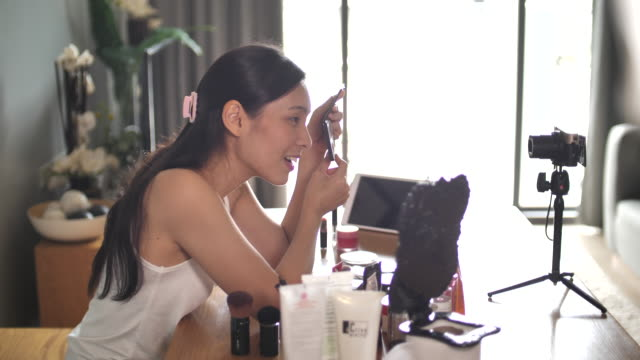 young asian woman making make-up tutorial on her video blog - tutorial stock videos & royalty-free footage